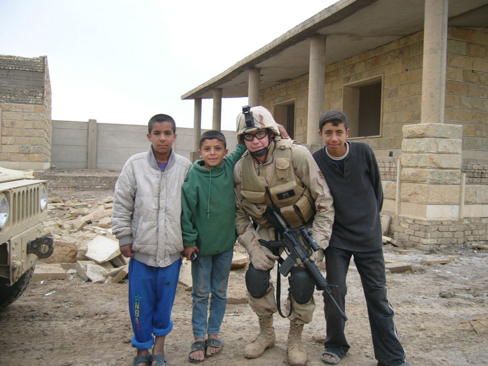 Adam with local Iraqi kids after removing explosive ordnance from near their house.